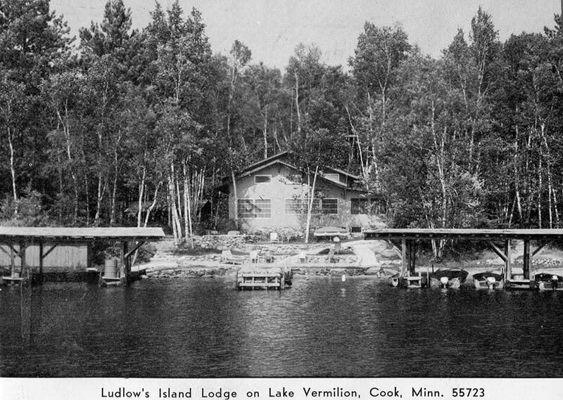 Old photo of lodge, dock and lake.