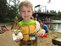 boy with wooden sailboat and trophy.